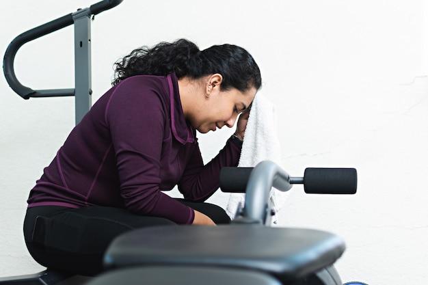 Een jonge vrouw veegt het zweet van haar voorhoofd met een handdoek tijdens een pauze in de sportschool