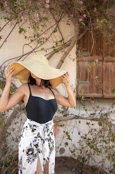 Een jonge vrouw verbergt zich voor de zon onder een grote strooien hoed bij een muur die verstrengeld is met droge takken van een bloeiende boom.