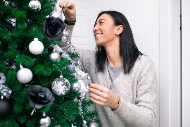 Een jonge vrouw versiert de kerstboom, ter voorbereiding op de viering van het nieuwe jaar. vrouw versieren een kerstboom. het mooie meisje glimlacht en heeft plezier tijdens de kerstvakantie.