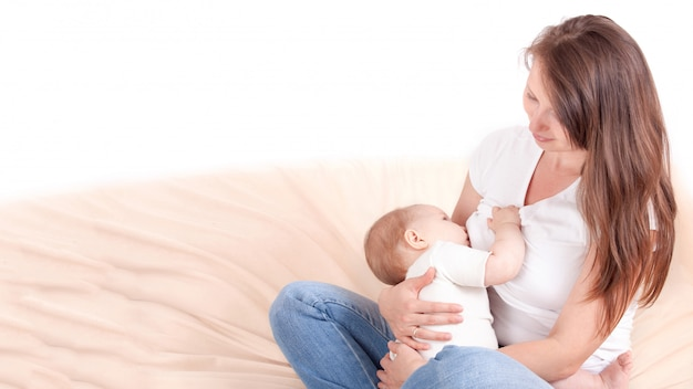 Een jonge vrouw voedt de borst van de baby, zittend op het bed. met vrije tekstruimte.