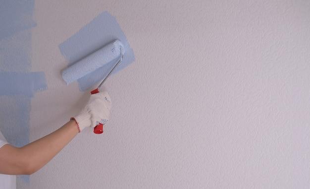 Een jonge vrouw voert reparaties uit in het appartement en schildert de muren blauw.