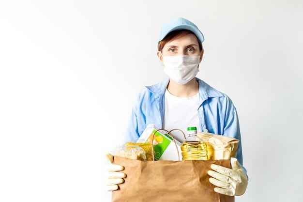 Een jonge vrouw vrijwilliger in een blauw uniform en een medisch masker en handschoenen houdt een papieren zak met voedsel.