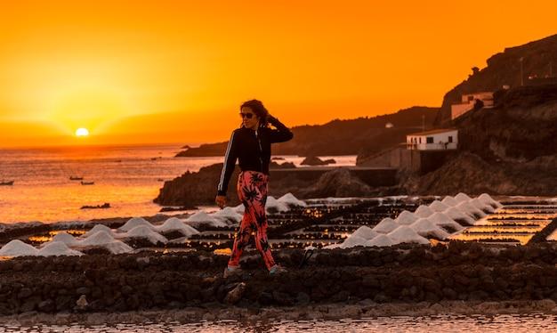 Een jonge vrouw wandelen in de oranje zonsondergang in de salina en op de achtergrond de fuencaliente-vuurtoren op de route van de vulkanen ten zuiden van het eiland la palma, canarische eilanden, spanje