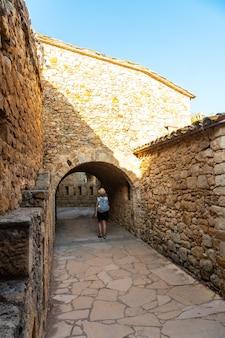 Een jonge vrouw wandelen in het middeleeuwse dorp pals, straten van het historische centrum bij zonsondergang, girona aan de costa brava van catalonië in de middellandse zee