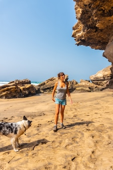 Een jonge vrouw wandelen met de hond aan zee in playa de garcey, westkust van fuerteventura, canarische eilanden. spanje