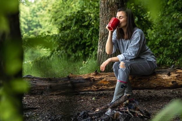 Een jonge vrouw warmt zich op bij een uitgedoofd vuur met een kopje verwarmende drank in het bos tussen de bomen