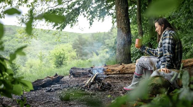 Een jonge vrouw warmt zich op bij een uitgedoofd vuur met een kopje verwarmende drank in het bos tussen de bomen.