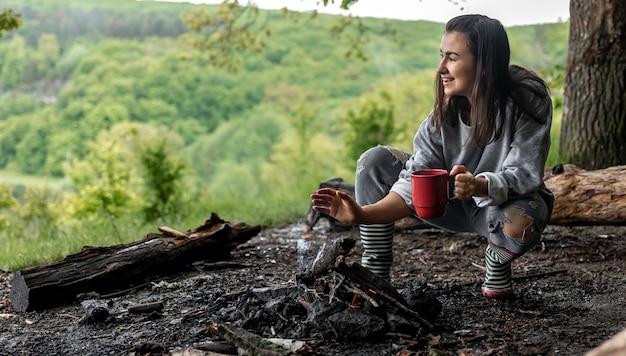 Een jonge vrouw warmt zich op bij het vuur met een kopje verwarmende drank in het bos