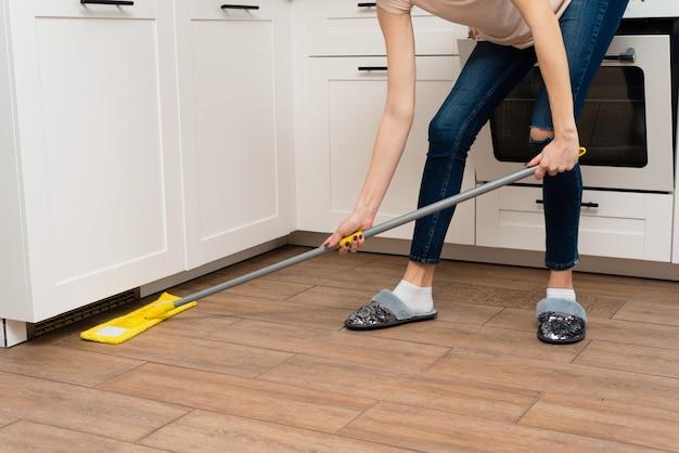Een jonge vrouw wast houten vloeren van een laminaat in een lichte keuken. het meisje wast stof en vuil onder de keukenkast vandaan