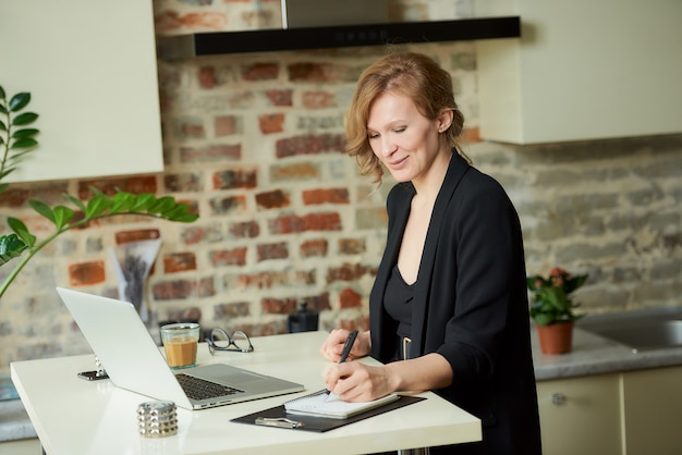 Een jonge vrouw werkt op afstand aan een laptop in haar keuken. een vrouwelijke baas is blij met haar medewerkers tijdens een videoconferentie thuis.