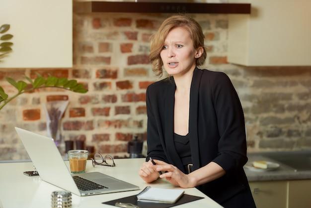 Een jonge vrouw werkt op afstand aan een laptop in haar keuken. een vrouwelijke baas stelde haar medewerkers teleur tijdens een videoconferentie thuis.