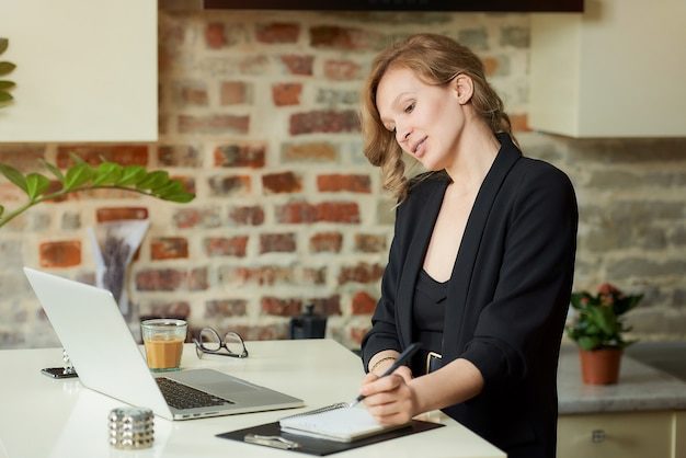 Een jonge vrouw werkt op afstand in haar keuken. een vrouwelijke baas die aantekeningen maakt in een notitieboekje terwijl haar werknemers thuis op een videoconferentie handelen.