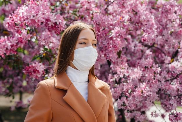 Een jonge vrouw zet haar masker af en haalt diep adem na het einde van de pandemie op een zonnige lentedag, voor bloeiende tuinen. bescherming en preventie covid 19.