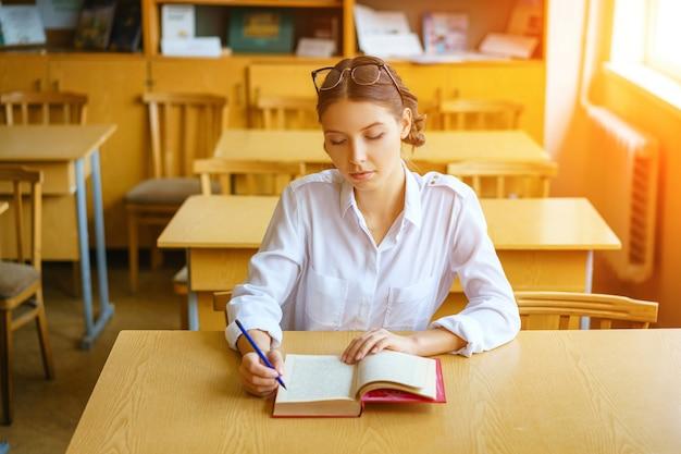 Een jonge vrouw zit aan een bureau in een wit overhemd