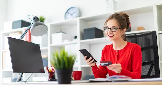 Een jonge vrouw zit aan het bureau op kantoor, met een bankkaart en telefoon in haar hand.