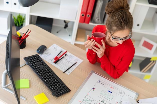 Een jonge vrouw zit aan tafel op kantoor, houdt een kopje koffie en kijkt naar het magneetbord.
