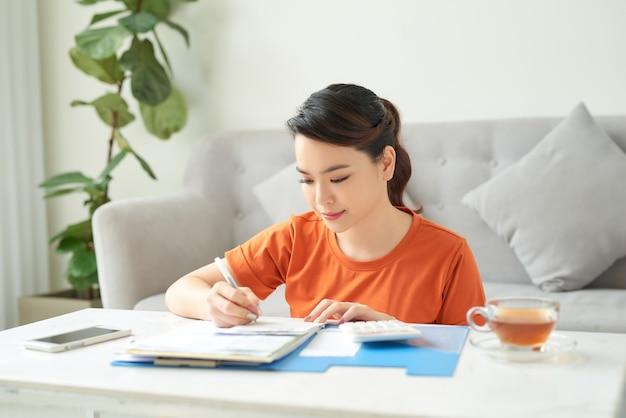 Een jonge vrouw zit in de woonkamer en kijkt thuis naar haar bonnetjes