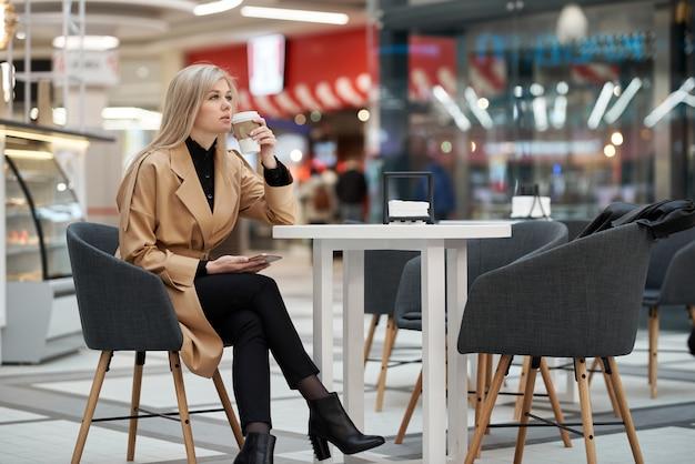 Een jonge vrouw zit in een café een winkelcentrum, praat op mobiele telefoon en houdt een papieren kopje koffie in haar hand.