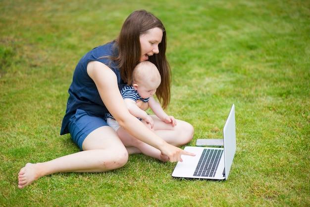 Een jonge vrouw zit in een weiland met een laptop en praat op een online conferentie met collega's op het werk. werken op afstand in de natuur. vrouwelijke student studeert op laptop op het gras