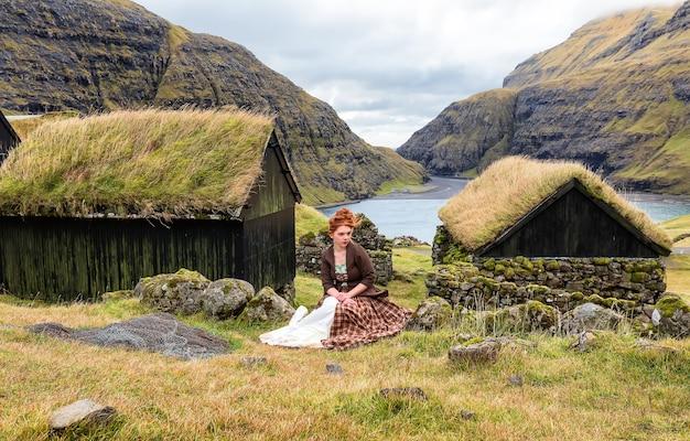 Een jonge vrouw zit in ouderwetse kleren op een stenen hek, in het dorp saksun. faeröer