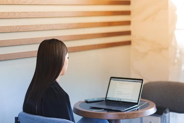 Een jonge vrouw zit met een laptop en een telefoon aan een tafel in een café. uitzicht vanaf de achterkant.