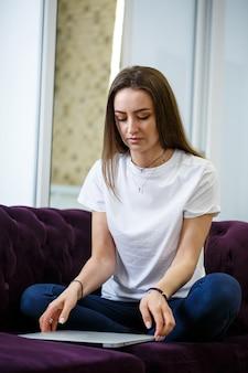 Een jonge vrouw zit op de bank en werkt op afstand van haar werk op een laptop. meisje met een computer op haar knieën die naar de monitor kijkt