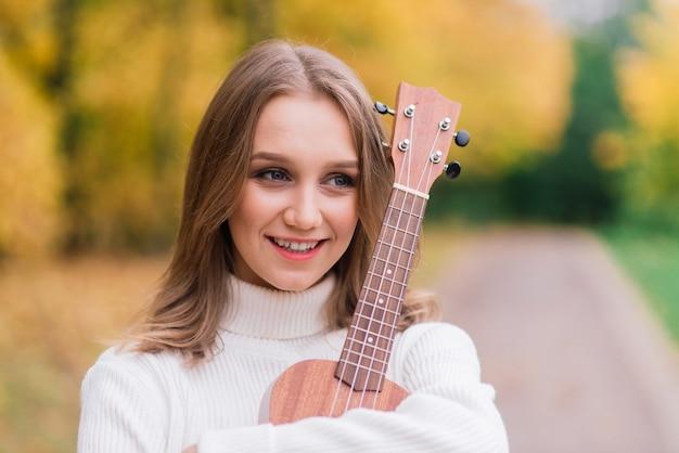 Een jonge vrouw zit op de bank in het park en speelt ukelele, poseren met gitaar