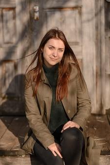 Een jonge vrouw zit op de trappen van een houten huis ingang.