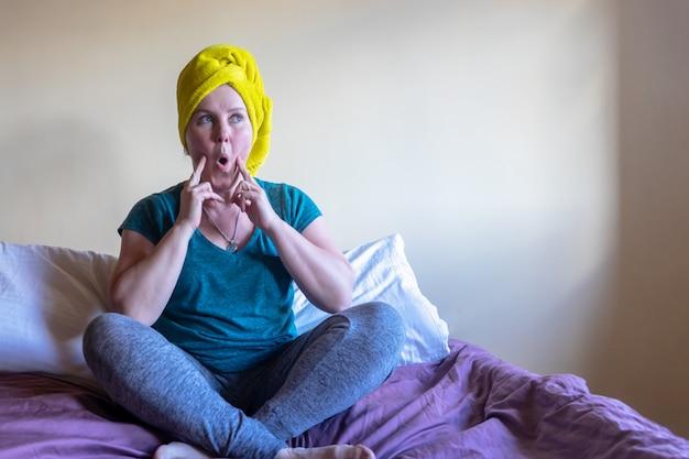 Een jonge vrouw zit op een bed en doet gymnastiek voor haar gezicht. het concept van quarantaine en zelfisolatie.
