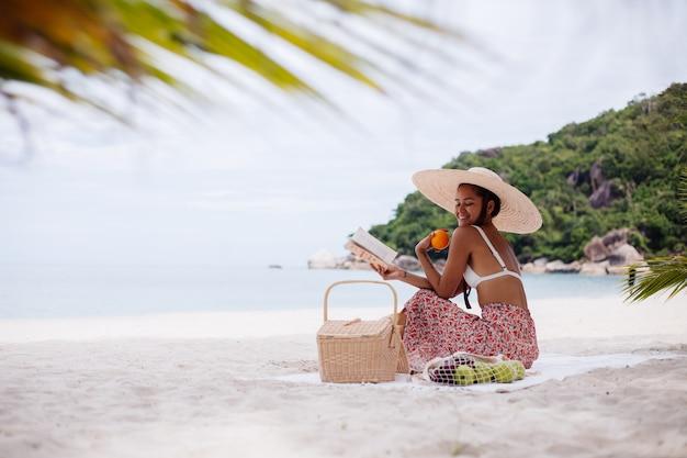 Een jonge vrouw zit op het strandtapijt in een strohoed en witte gebreide kleren