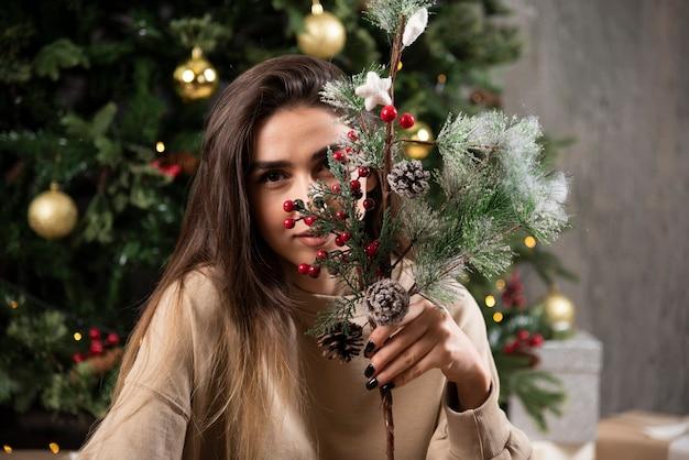 Een jonge vrouw zit op pluizig tapijt met kersthulstbessen.