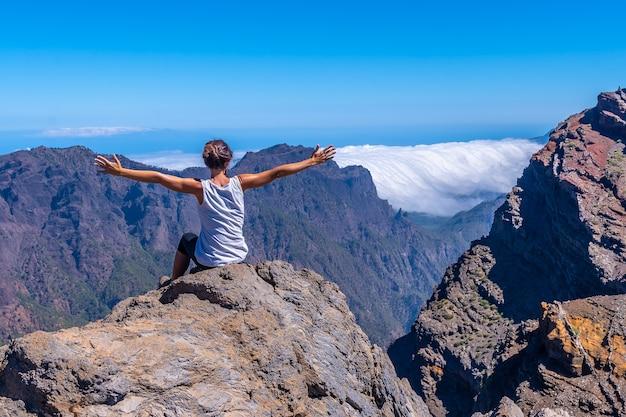 Een jonge vrouw zit uit te rusten en te kijken naar het uitzicht op het roque de los muchachos nationaal park bovenop de caldera de taburiente, la palma, canarische eilanden. spanje