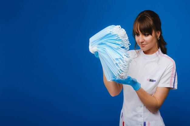 Een jonge vrouwelijke arts heeft veel maskers in haar handen. een verpleegster in een wit pak op een blauwe achtergrond met maskers in haar handen
