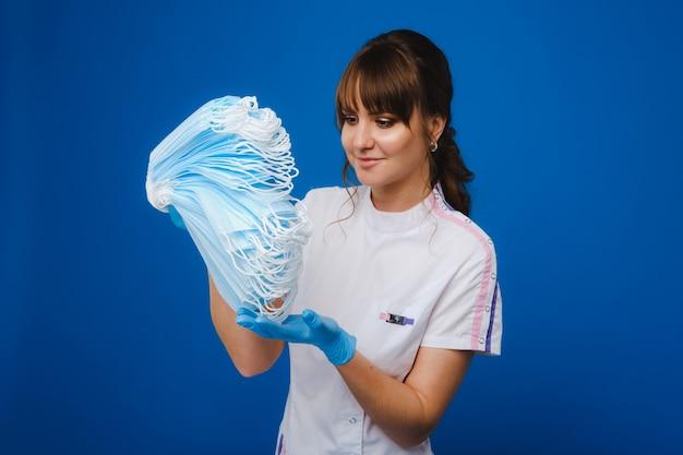 Een jonge vrouwelijke arts heeft veel maskers in haar handen. een verpleegster poseert op een blauwe achtergrond