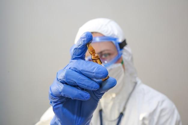 Een jonge vrouwelijke arts in een beschermend pak houdt een ampul met medicijnen in haar hand