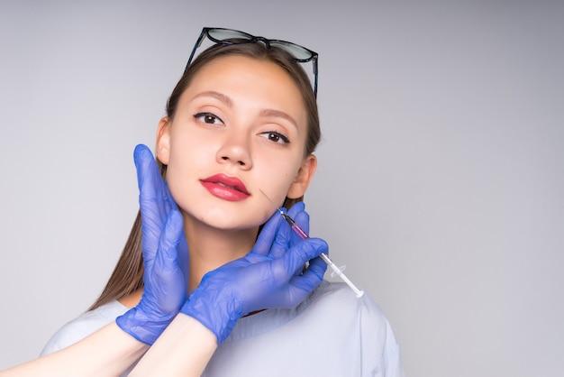 Een jonge vrouwelijke arts met een bril bevestigde een spuit op haar gezicht en staarde aandachtig naar de camera. geïsoleerd op een grijze achtergrond
