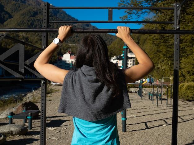 Een jonge vrouwelijke atleet doet pullups op een achteraanzicht van een horizontale balk