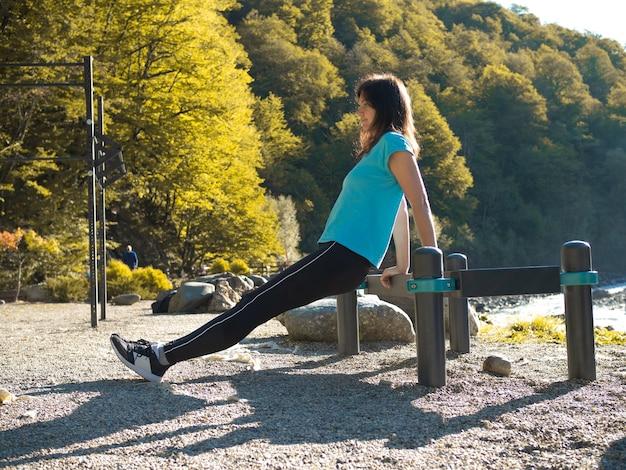 Een jonge vrouwelijke atleet doet push-ups vanaf de bank. buitensportactiviteiten.