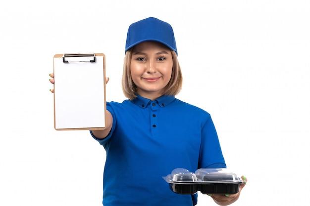 Een jonge vrouwelijke koerier van het vooraanzicht in blauw uniform de leveringskom en blocnote van de holdingsvoedsel voor handtekeningen