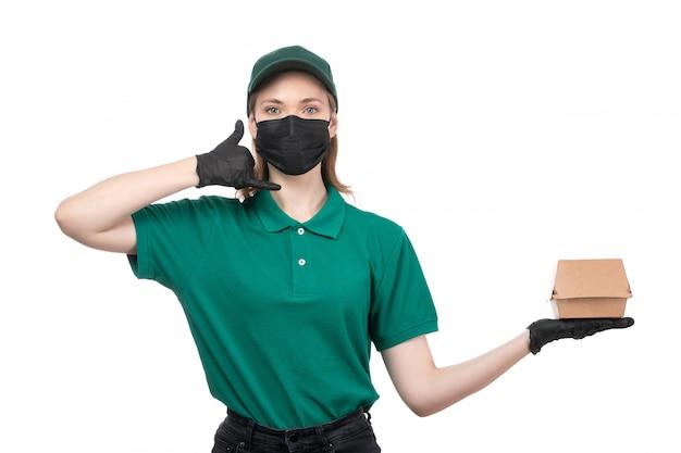 Een jonge vrouwelijke koerier van vooraanzicht in groene uniforme zwarte handschoenen en het zwarte pakket van de de voedsellevering van de maskerholding leveren