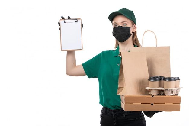 Een jonge vrouwelijke koerier van vooraanzicht in groene uniforme zwarte handschoenen en zwart masker die de pakketten van de voedsellevering het bezorgen houden