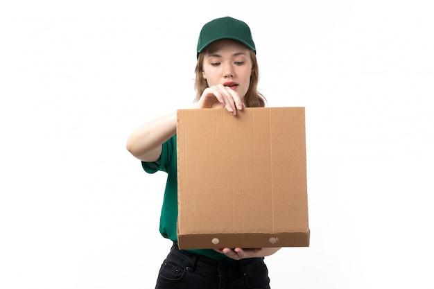 Een jonge vrouwelijke koerier vooraanzicht in groen uniform glimlachend holdingspakket met voedsel dat het opent