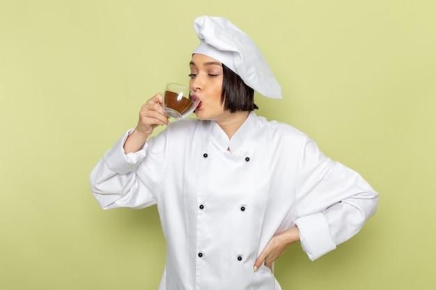 Een jonge vrouwelijke kok van vooraanzicht in wit kokkostuum en glb die en kop van poederkoffie op de groene muur houden