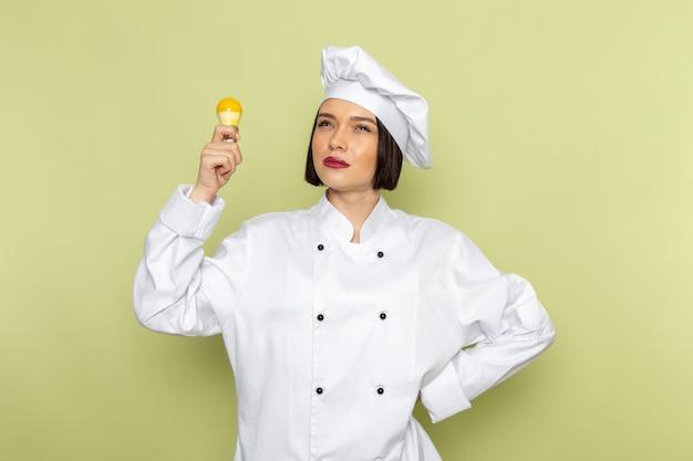 Een jonge vrouwelijke kok van vooraanzicht in wit kokkostuum en glb die gele gloeilamp op de groene muur van het dameswerk de kleur van de voedselkeuken houden