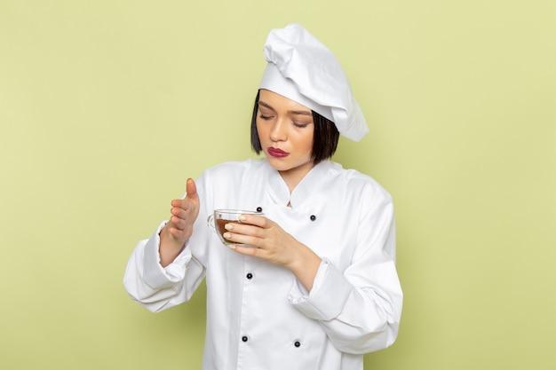 Een jonge vrouwelijke kok van vooraanzicht in wit kokkostuum en glb die kop van poederkoffie op de groene muur houden