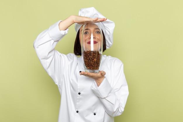 Een jonge vrouwelijke kok van vooraanzicht in wit kokkostuum en glb-holdingskruik met koffiezaden op de groene muur de kleur van de het voedselkeuken van het damewerk