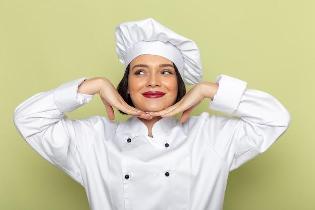 Een jonge vrouwelijke kok van vooraanzicht in wit kokskostuum en glb die op verleidelijke manier op de groene muur de kleur van de het voedselkeuken van het muurdame stellen