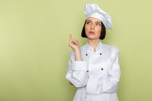 Een jonge vrouwelijke kok van vooraanzicht in wit kookkostuum en pet in denken stelt op de groene muur de kleur van de het voedselkeuken van het dameswerk