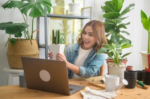 Een jonge vrouwelijke ondernemer die met een laptop werkt, presenteert kamerplanten tijdens een online livestream thuis