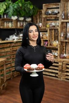 Een jonge vrouwelijke serveerster serveert koffie aan een klant in een kartonnen wegwerpbeker en dessert